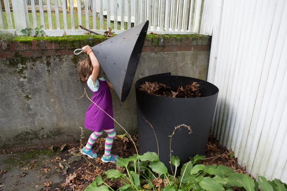 Abby Edelstein, 5, closed the lid on her back yard compost pile in Newton.