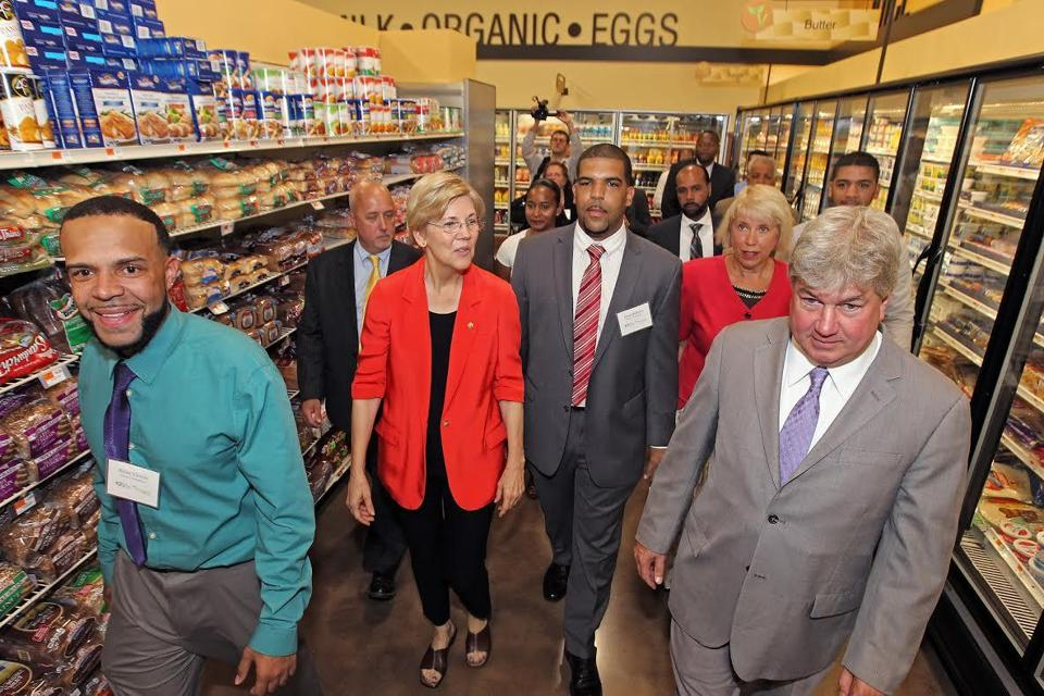 Taking a look around Vicente's Tropical Grocery in Brockton on Sept. 3 were (from left to right) store director Brian Vicente, Brockton Mayor Bill Carpenter, US Senator Elizabeth Warren, store owner Jason Barbosa, Brockton Neighborhood Health Center chief executive officer Sue Joss, and state Representative Michael Brady of Brockton. (Boston Local Initiatives Support Corporation photo)