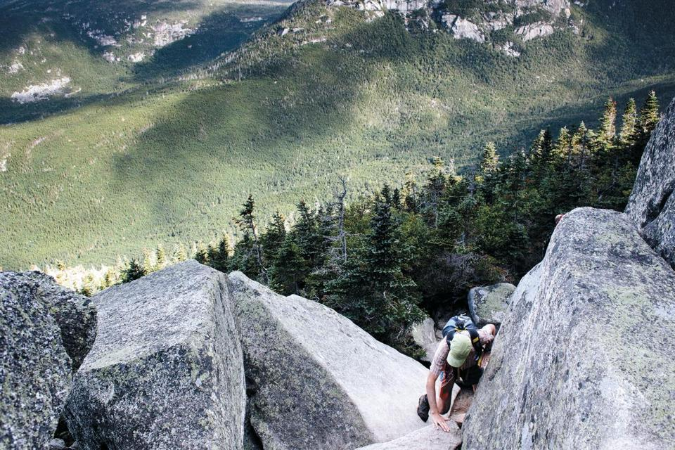 William Young climbs the final segments of Mount Katahdin in Maine, the iconic northern terminus of the Appalachian Trail, Aug. 14, 2015. Faced with increasing crowds and partylike behavior by a few, officials are threatening to reroute the end of the trail off Katahdin — a proposal that has stunned the hiking world. (Tristan Spinski/The New York Times)