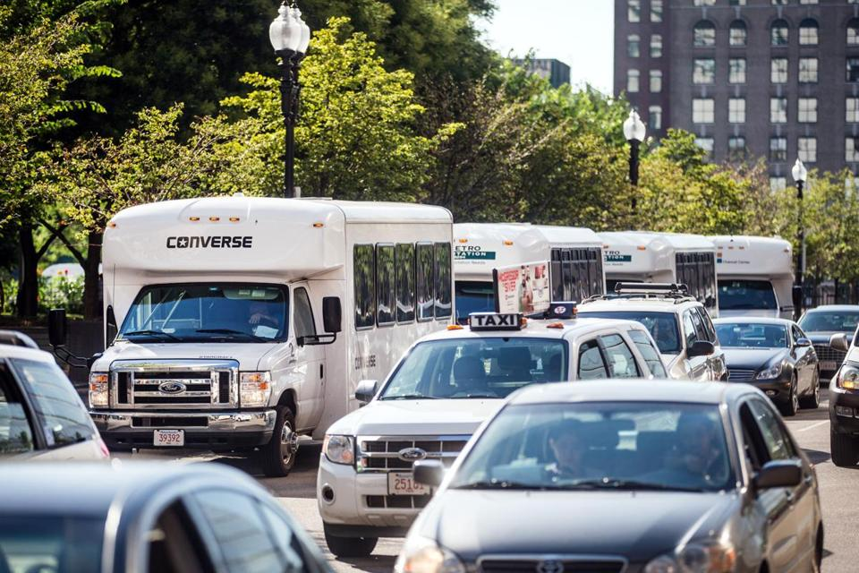 Private shuttle buses along Summer Street for company employees supplement MBTA routes.