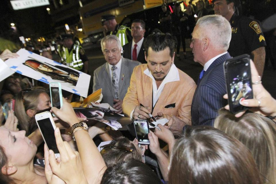 Depp signed autographs for fans upon leaving the theater.
