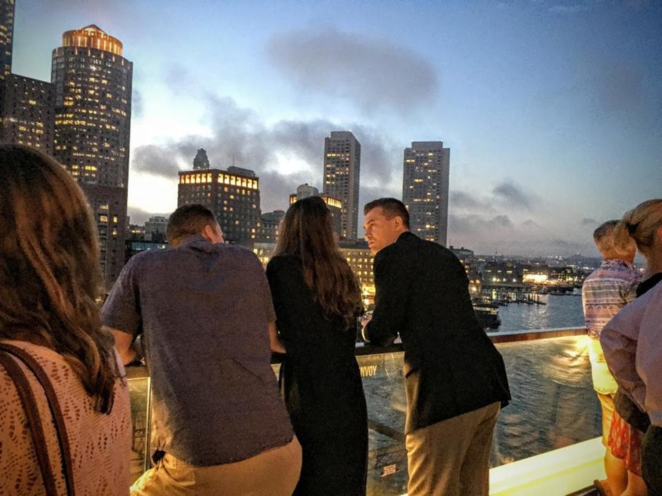 Patrons drink in a view of Boston's skyline from the Envoy Hotel's Lookout rooftop bar.