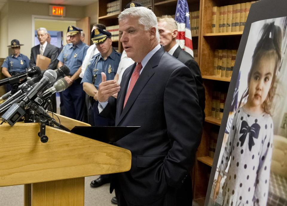 Suffolk County District Attorney Daniel F. Conley spoke at a press conference. A photo of Bella Bond was placed beside him.
