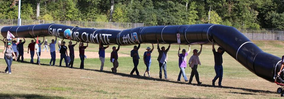 Protesters carried an inflatable pipeline from Billings Field to the proposed site of the metering and regulating station.