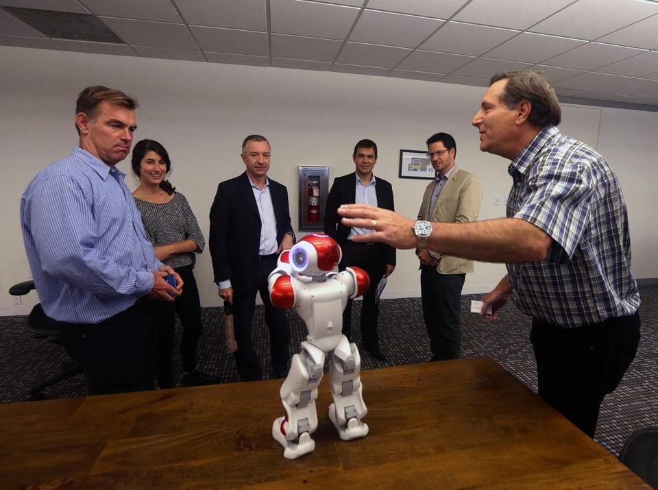 Mark Williams (far right), president and CEO of Canadian startup RxRobots, spoke during a meeting at the Cambridge Innovation Center.