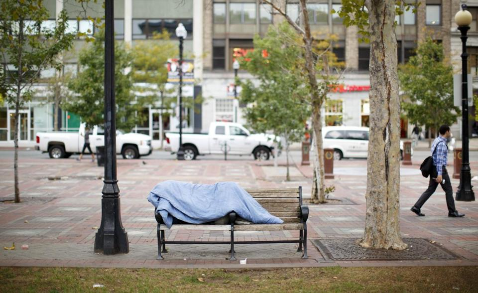 A homeless person slept on a bench in Copley Square.