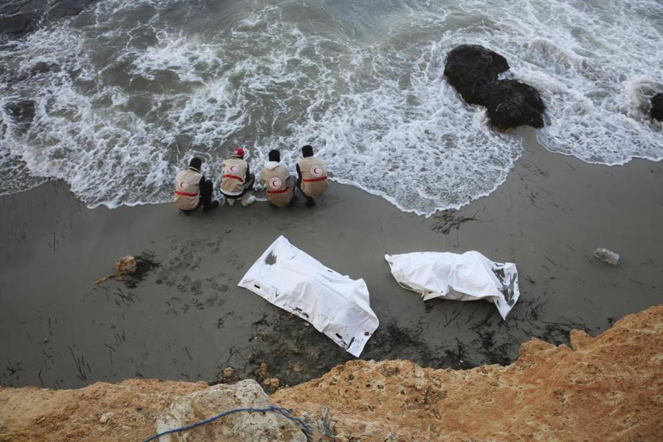 Libyan Red Crescent workers placed bodies washed ashore near Tripoli into bags. The bodies of 95 migrants were found near a smugglers' route.