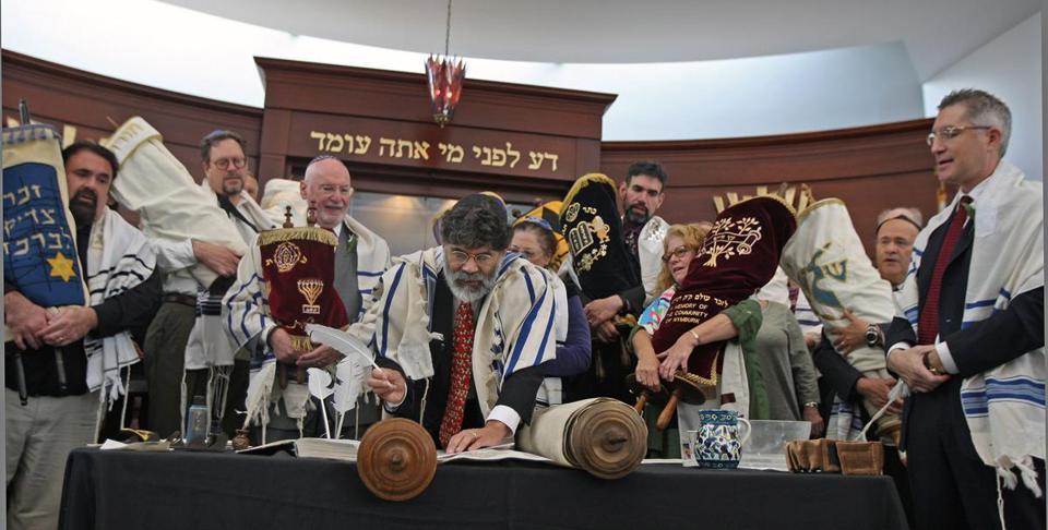 At Temple Sinai in Sharon, a completion ceremony was held recently to mark the end of an 18-month project to restore a beloved Torah scroll that survived the Holocaust in Bohemia and Moravia. Torah scribe Rabbi Kevin Hale prepares to enter the second of three final letters to the scroll. Behind him are representatives of other area congregations in possession of Czech Torah scrolls. (George Rizer for the Globe)