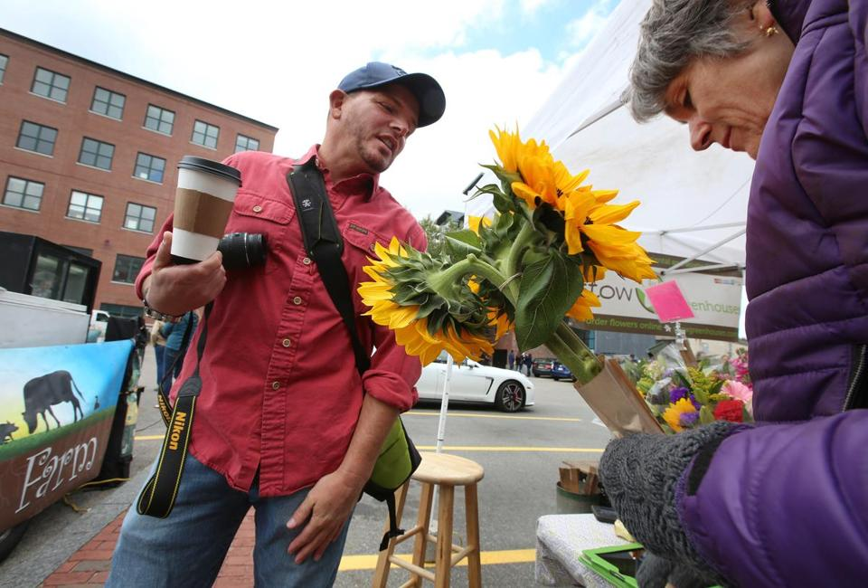 Chris Masci, owner of New England Open Markets, chatted with Barbara Rietscha, owner of Stow Greenhouses. The South End Open Market at SoWa will move to a new location next year.