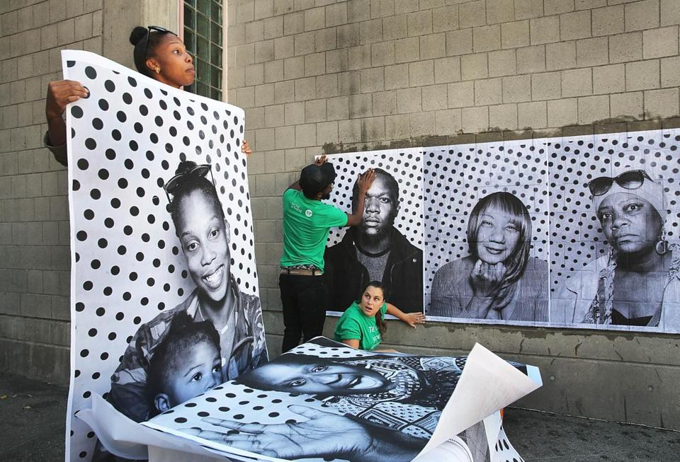 Aziza Robinson-Goodnight held up a giant xerox photo of herself and daughter August, 15 months, as volunteers pasted pictures of neighborhood residents on a wall outside the Boston Public Library in Roxbury.