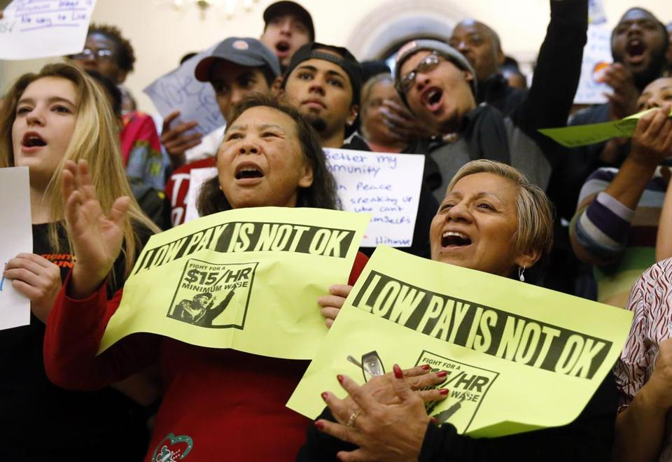Workers cheered a proposal for a $15 minimum wage during a rally Tuesday at the State House. Industry groups oppose the measure, saying it would hurt business.