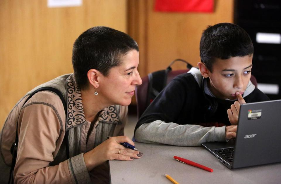 Boston, MA--10/15/2015--EdVestors (cq) president and CEO Laura Perille (cq) looks in on 12-year-old sixth-grader David Iovanna (cq). Students at TechBoston Academy use technology, from EdVestors, to learn math on Thursday, October 15, 2015. Photo by Pat Greenhouse/Globe Staff Topic: 19edvestors Reporter: Jeremy Fox