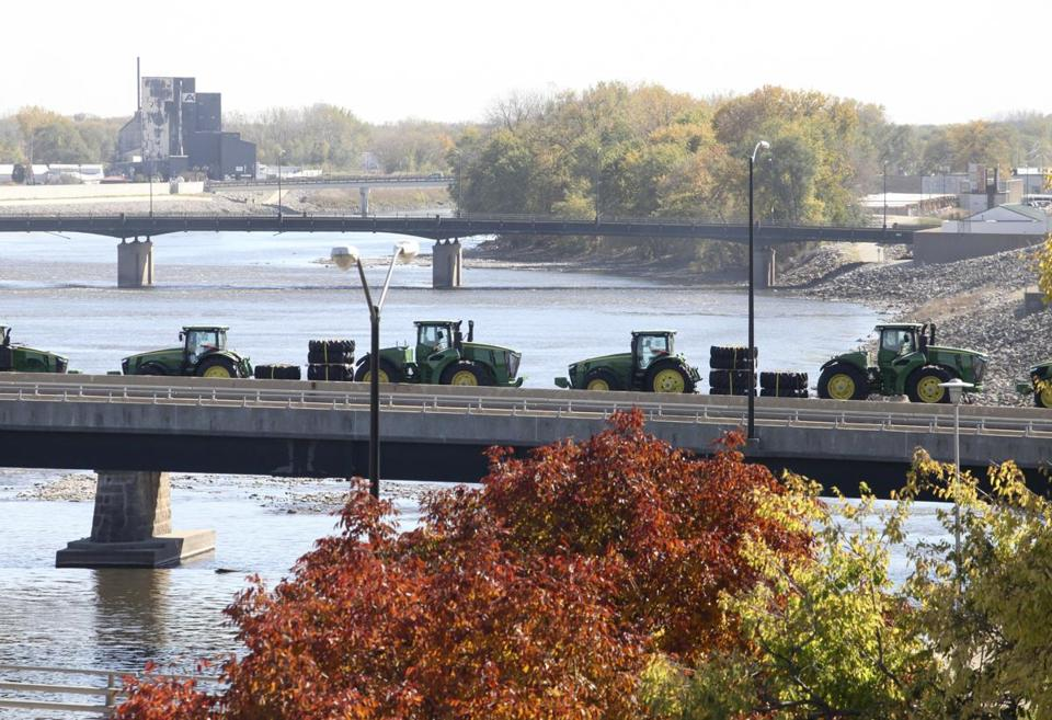 WATERLOO, IA - OCTOBER 14: John Deere tractors are transported by rail across the Cedar River, on October 14, 2015, in Waterloo, Iowa. (Matthew Holst for the Boston Globe)