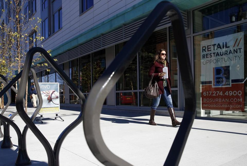 A woman walked past the Vivo Apartment Homes on Third Street in Cambridge Monday. Rents for reserved units there will range from $1,996 to $2,439 for two-bedroom apartments.