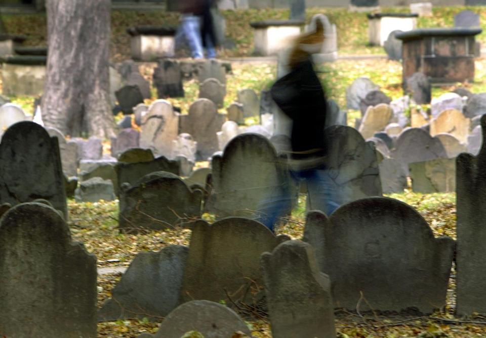 A ghost of a visitor walks through Boston's historic Granary Burying Ground on a Halloween past.