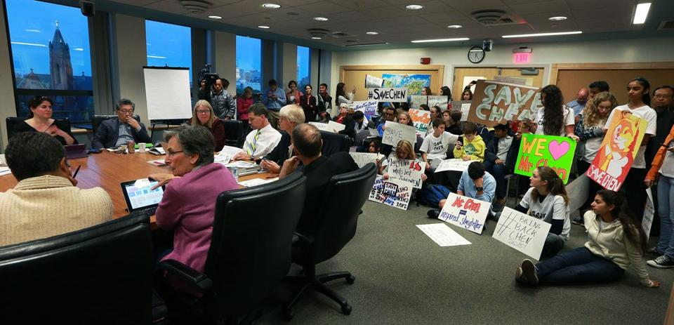 Supporters of Brookline teacher Larry Chen mobbed a school committee meeting earlier this month. Chen has not been terminated, Brookline's interim superintendent said Tuesday, and will return to the classroom on Nov. 5.