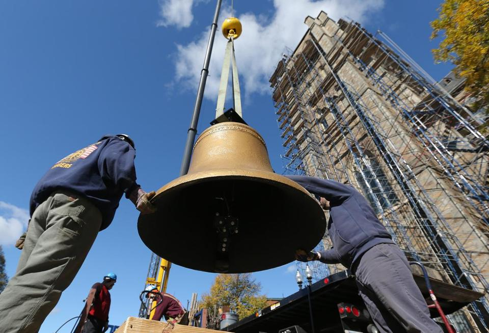 Workers prepared one of the historic bells to be hoisted.