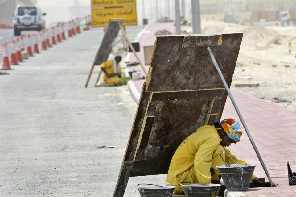 A laborer in Dubai avoided the sun on a scorching June day by working behind a wooden sign.