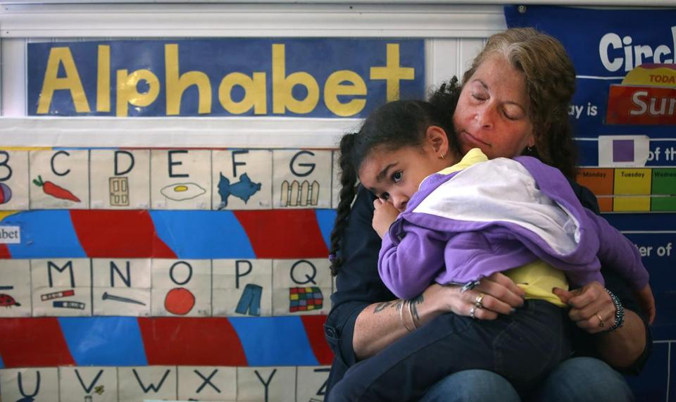 Avery Gormely, 4, needed comforting from teacher Kerrelle Dow at Little Discoveries child care in Brockton in May.