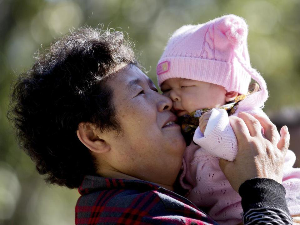 In this 2012 file photo, a Chinese woman played with her grandchild at the Ritan Park in Beijing.