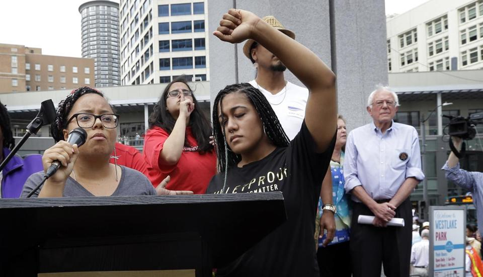 Marissa Johnson (left) spoke as Mara Jacqueline Will held her fist overhead as the two women took over the microphone at an August rally in Seattle for Senator Bernie Sanders (right).