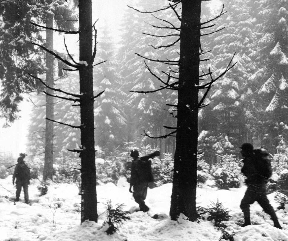 Infantrymen of the US First Army in Belgium's Ardennes Forest as they advance to contact German forces at the start of the Battle of the Bulge.