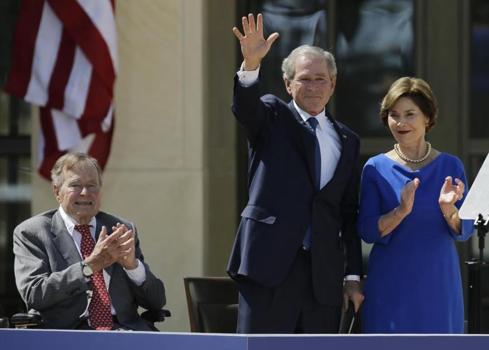 FILE - In this April 25, 2013, file photo, Former President George H.W. Bush, left, applauds with Laura Bush after former President George W. Bush's speech during the dedication of the George W. Bush Presidential Center in Dallas. Former President George H.W. Bush is publicly criticizing for the first time key members of his son's administration. A biography of the nation's 41st president to be published in November, 2015, contains his sharply critical assessments of former Vice President Dick Cheney and Defense Secretary Donald Rumsfeld. (AP Photo/David J. Phillip, File)