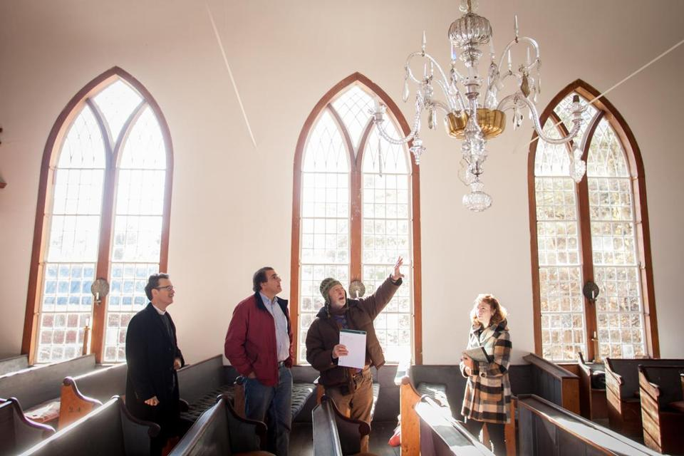 Conservator Brian Powell (second from right) talked about artifacts of the shuttered St. Paul's Church in Otis Monday with (from left) the Reverend Stephen T. Ayres of Old North Church; Steven Abdow, an Episcopal official; and colleague Lauren Drapala.