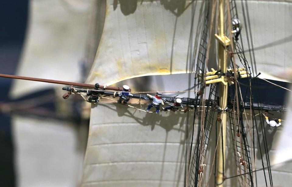 A close-up shows the details of miniature sailors aboard a model of the USS Constitution.