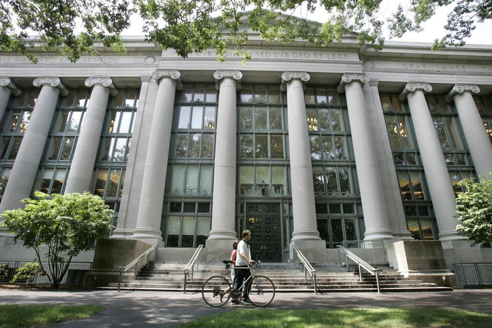 A bicyclist walked by Langdell Hall, the Harvard Law Library, on the campus of Harvard Law School.