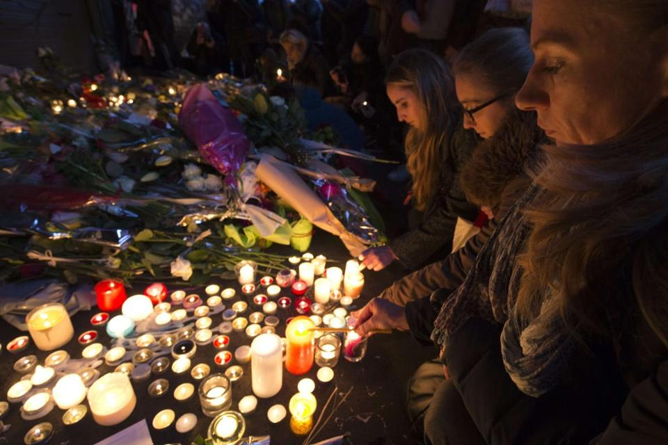 People lit candles Saturday at a makeshift memorial on the Rue de Charonne in Paris to the victims of the attacks.