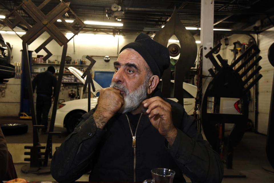 Mahmood demonstrates how he used a pistachio shell to whistle when he was a child. He was sitting at a table in the gallery section of his auto shop.