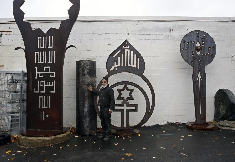 Mahmood Rezaei-Kamalabad, with some of his artwork, and the pipe he wants to be buried in, outside Aladdin Auto Service in Cambridge.