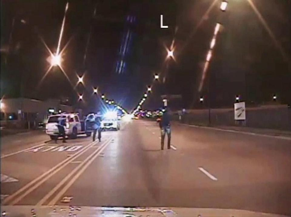 Laquan McDonald (right) walked on a road before he was fatally shot 16 times last year by Chicago Police Officer Jason Van Dyke.