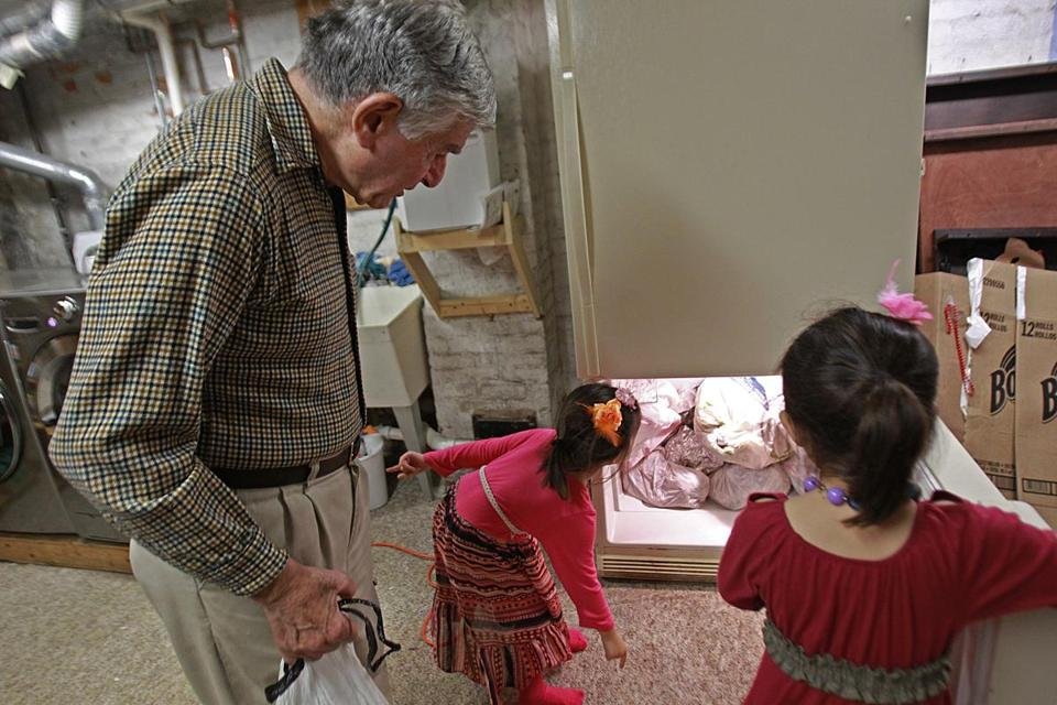 Former Governor Michael Dukakis helped his neighbors, Lilac and Isabella Nguyen, get the donated turkey carcasses into a freezer.