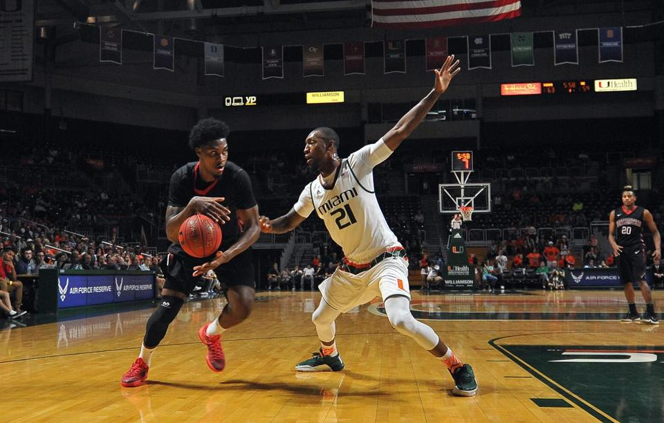 Miami Kamari Murphy (21) blocks Northeastern Quincy Ford who tries to drive to the basket during the second half of an NCAA college basketball game in Coral Gables, Fla., Friday, Nov. 27, 2015. (AP Photo/Gaston De Cardenas)