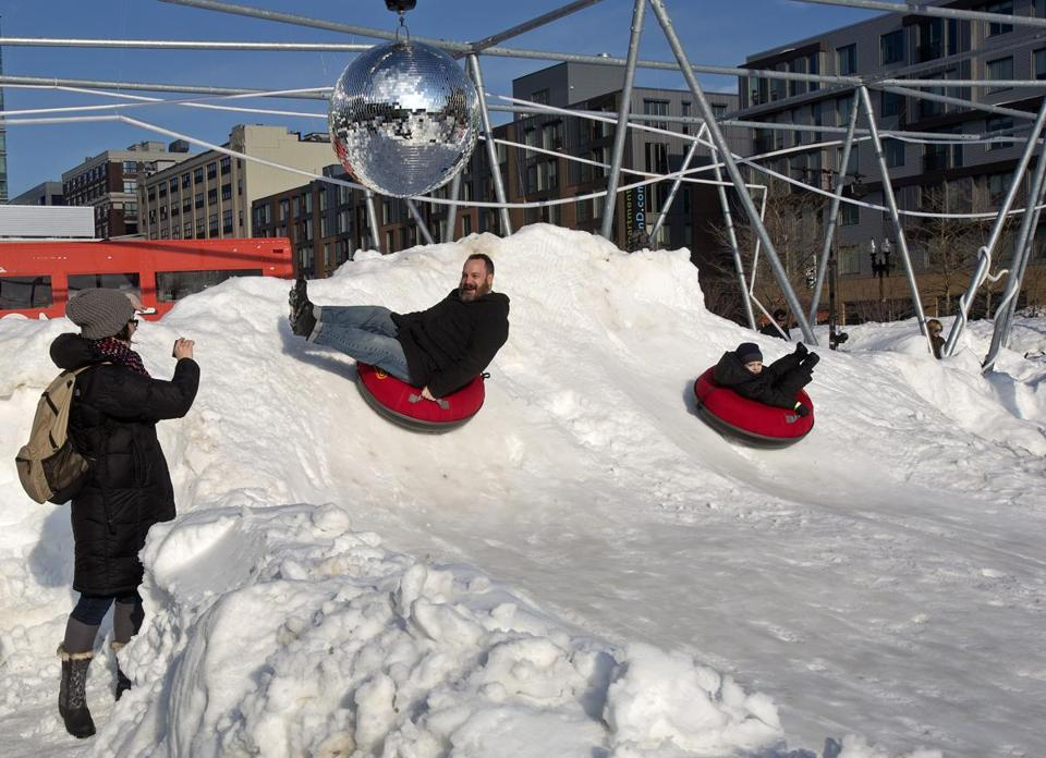 Tim Conway (top) and his son Eamon, 5, of Charlestown rode sleds at the Lawn on D's Slope Fest last February.