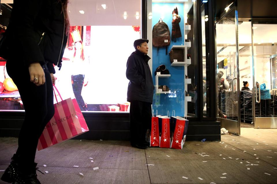 Tom Nguyen, with three bags from Downtown Crossing stalwart Macy's, waited for the rest of his family to return from shopping on Black Friday.