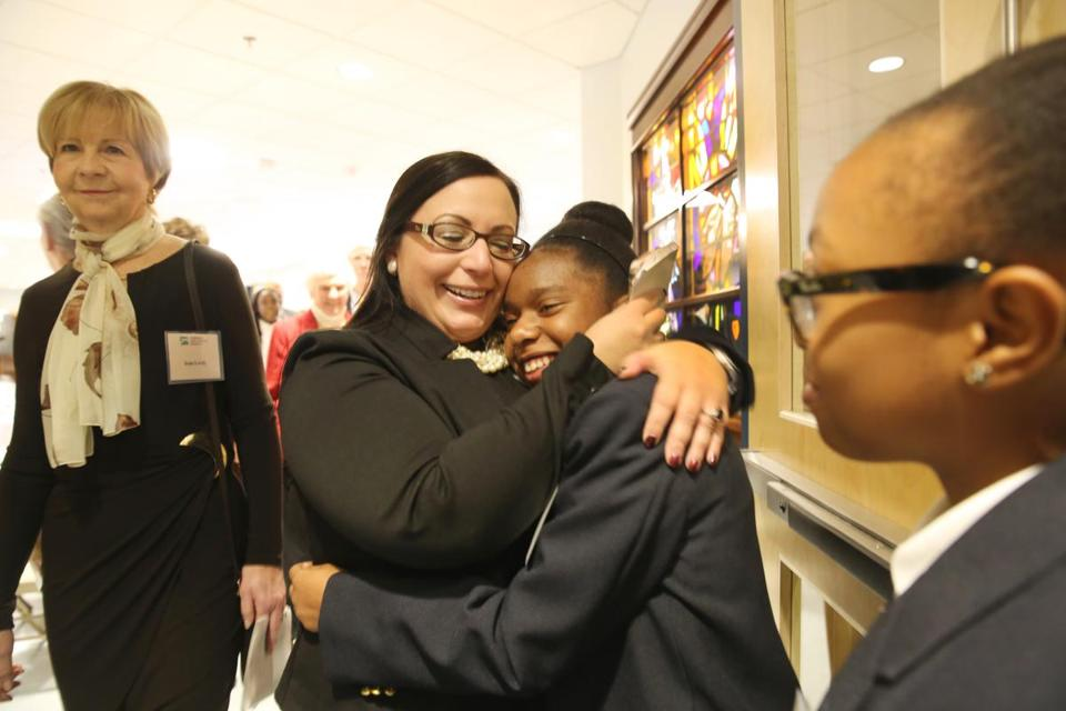 Principal Lisa Warshafsky hugged student Orianeh Byron-Gabelus on Wednesday at the rededication of the Lower Mills campus of St. John Paul II Catholic Academy.