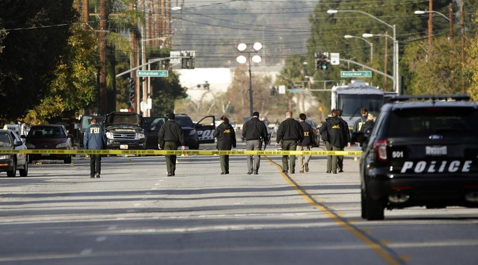 Investigators searched for bullet casings at the scene of Wednesday's police shootout in San Bernardino, Calif., on Thursday.