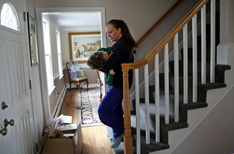 Dawn Giordano, a day nurse, carried 6-year-old Matthew Davidopoulos downstairs to his wheelchair. Matthew suffers from spinal muscular atrophy, a rare disease that causes loss of muscle control.
