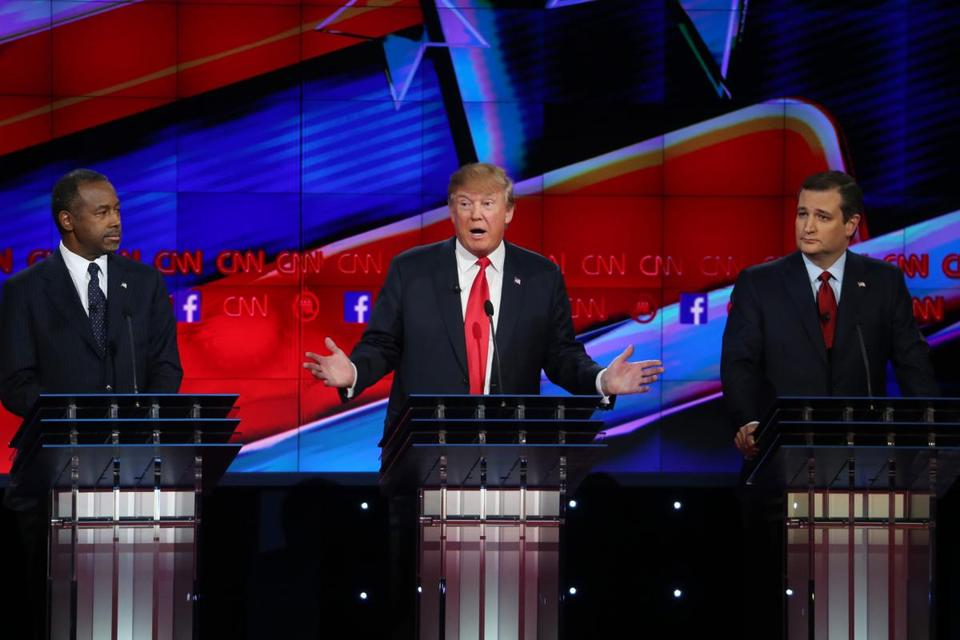 Republican presidential candidate Donald Trump (center) spoke as Ben Carson (left) and Ted Cruz (right) listened.