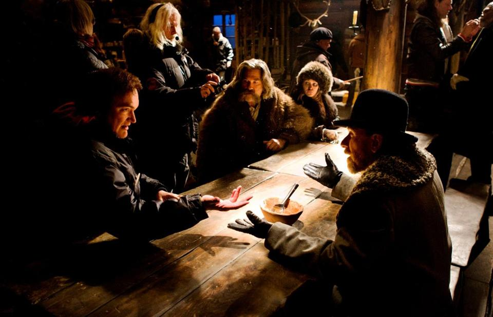 "Quentin Tarantino (sitting, far left) directing a scene for his new movie, ""The Hateful Eight."""