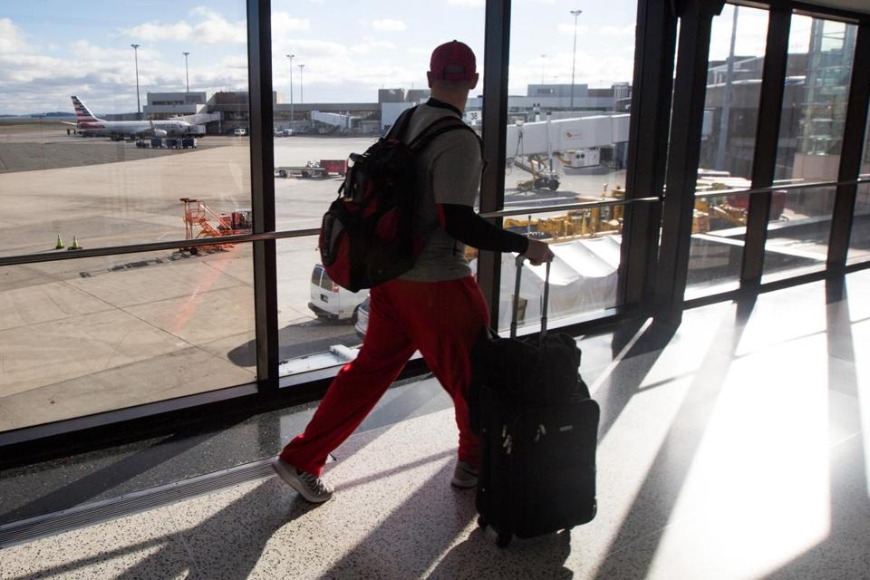 A traveler made his way through a hall way overlooking a tarmac at Logan International Airport.