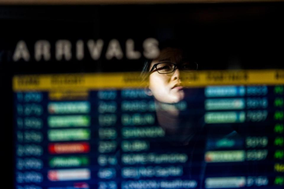 A woman is reflected in the arrivals board at Logan International Airport in Boston.