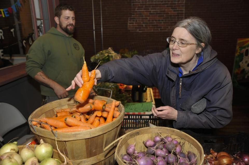 Customer Mary Talbot picked some fresh carrots as 4 Nichols watched at the Mill City Grows farmers market booth in Lowell. Mill City Grows hopes to bring fresh foods to more locations in Lowell if the Massachusetts Food Trust receives its authorized funding.