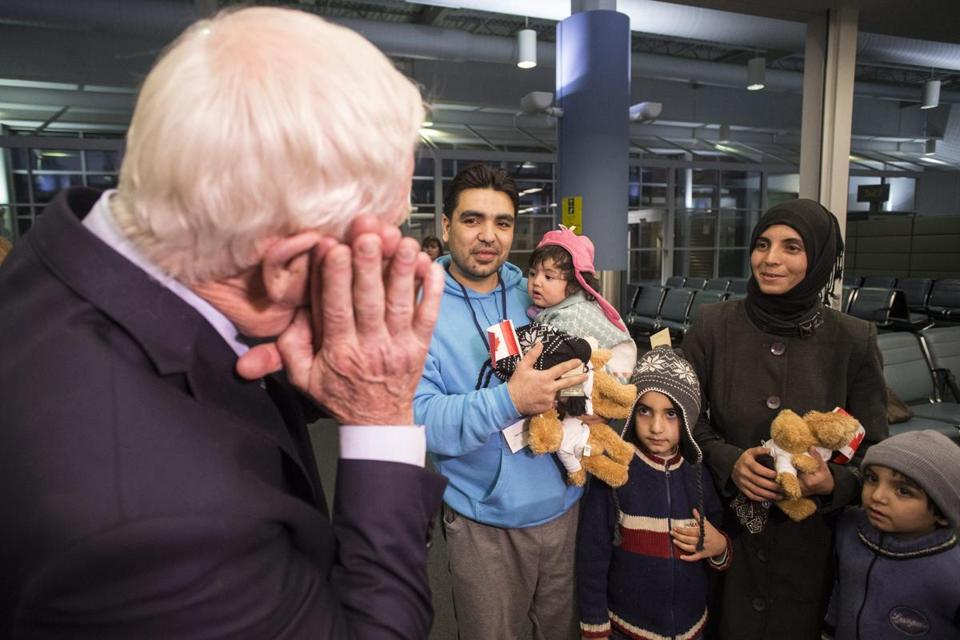 Canada's Governor General David Johnston (left) gestures to suggest 'rest' as a family Syrian refugees tell him they had been travelling for two days upon their at the Welcome Centre at Toronto's Pearson Airport on Friday, Dec. 18, 2015. (Chris Young/The Canadian Press via AP)