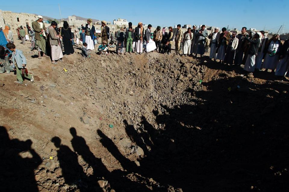 Yemenis gather around a crater reportedly caused by a Saudi-led airstrike targeting the outskirts of the capital Sanaa on Dec. 29.