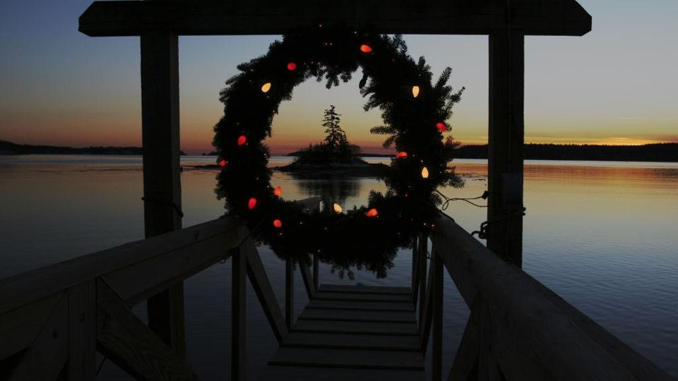 A Christmas wreath decorated with lights hung at the end of a dock in Maine.