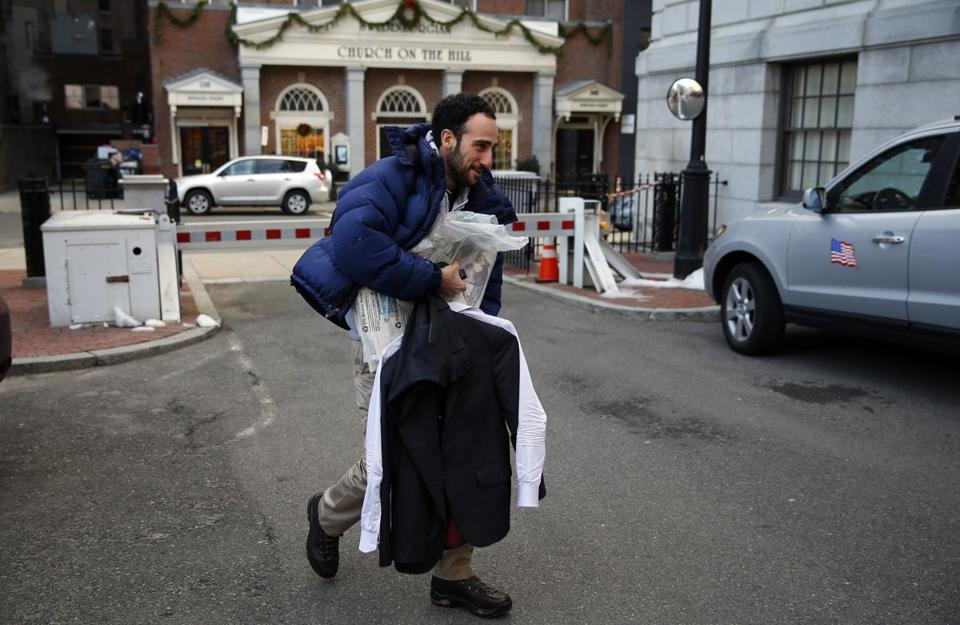 Boston, Massachusetts -- 1/3/2016- Boston Globe reporter Josh Miller carried his suit and a bundle of Sunday Boston Globes to the State House as he arrived for an interview after spending the early morning hours helping fellow journalists worked to deliver the Sunday Boston Globe in Boston, Massachusetts January 3, 2016. Jessica Rinaldi/Globe Staff Topic: Reporter:
